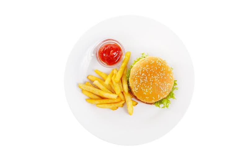 Burger και οι τηγανιτές πατάτες στο πιάτο απομόνωσαν το λευκό στοκ φωτογραφία με δικαίωμα ελεύθερης χρήσης
