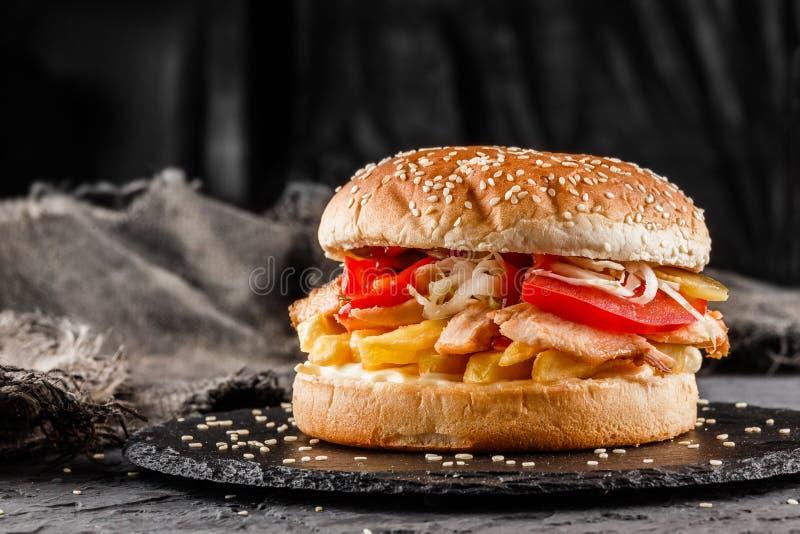 Burger κοτόπουλου με τις ντομάτες, τις τηγανιτές πατάτες και τη σάλτσα στη μαύρη πλάκα πέρα από το σκοτεινό υπόβαθρο food unhealt στοκ φωτογραφία