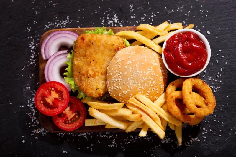 Burger κοτόπουλου με τις τηγανιτές πατάτες και τα δαχτυλίδια κρεμμυδιών, τοπ άποψη στοκ φωτογραφία με δικαίωμα ελεύθερης χρήσης