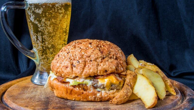 Burger με την πατάτα και την μπύρα στοκ εικόνες