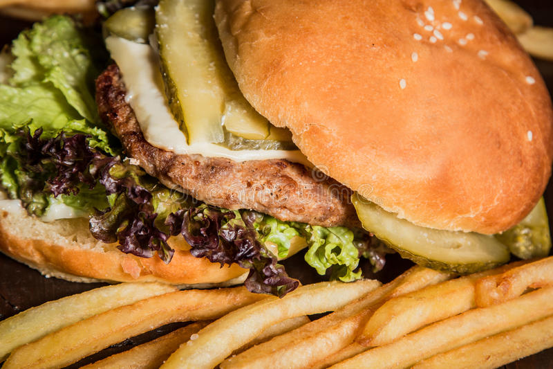 Burger με τις πατάτες στον πίνακα στοκ εικόνες