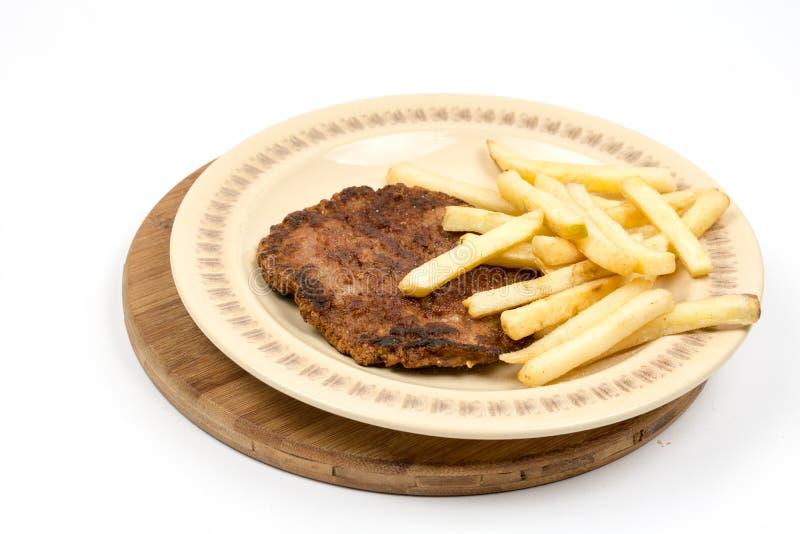Burger με τις τηγανιτές πατάτες που εξυπηρετούνται στο πιάτο Χάμπουργκερ κιμά με τις πατάτες που απομονώνονται πέρα από το άσπρο  στοκ φωτογραφία με δικαίωμα ελεύθερης χρήσης