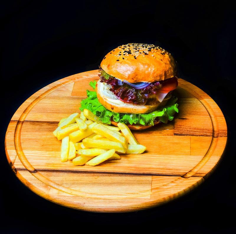 Burger με τις τηγανιτές πατάτες σε έναν ξύλινο πίνακα Γρήγορο φαγητό στοκ εικόνες