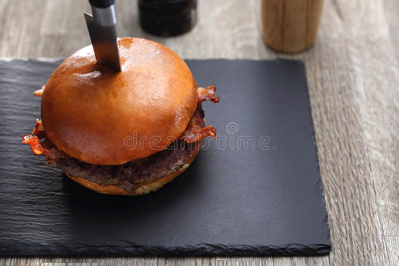 Burger με το μπέϊκον Ψημένο στη σχάρα cutlet βόειου κρέατος σε ένα κουλούρι στοκ φωτογραφία