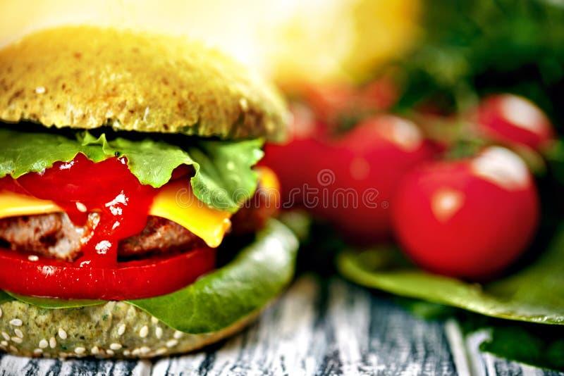 Burger με το πράσινο κουλούρι και τα φρέσκα λαχανικά στοκ εικόνα με δικαίωμα ελεύθερης χρήσης
