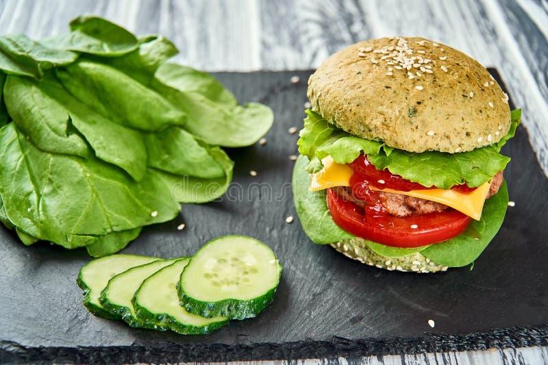 Burger με το πράσινο κουλούρι και τα φρέσκα λαχανικά στοκ φωτογραφίες