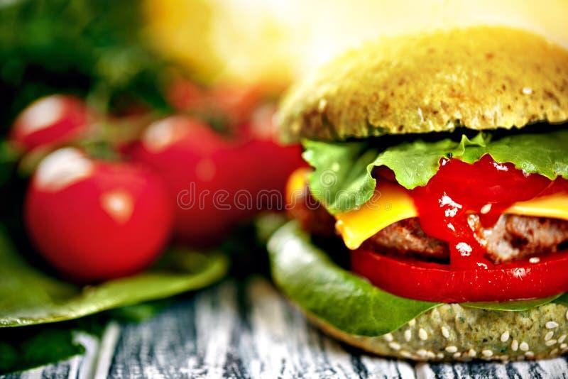 Burger με το πράσινο κουλούρι και τα φρέσκα λαχανικά στοκ φωτογραφία με δικαίωμα ελεύθερης χρήσης