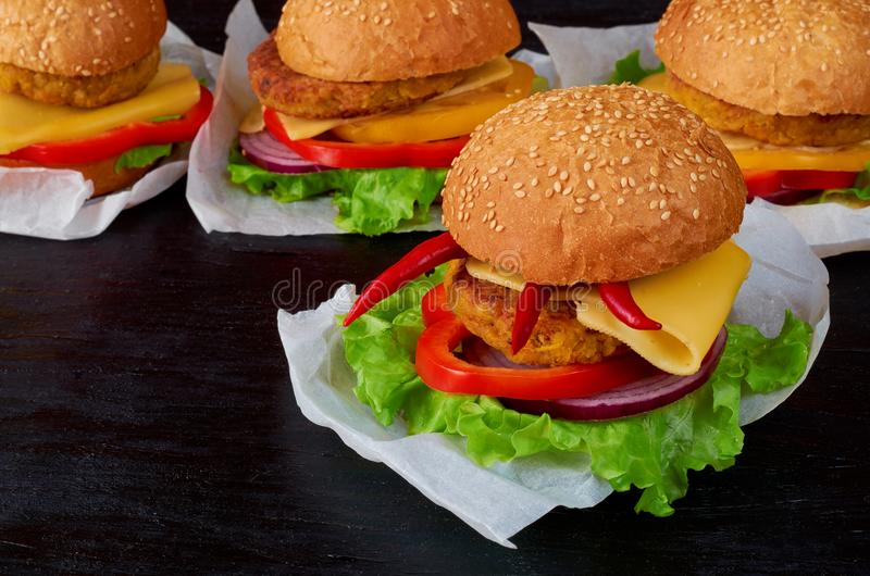Burger με το falafel, τη σαλάτα, τα δαχτυλίδια κρεμμυδιών, το τυρί, τις ντομάτες και το πιπέρι τσίλι στο μαύρο υπόβαθρο Κλασικό α στοκ φωτογραφία με δικαίωμα ελεύθερης χρήσης