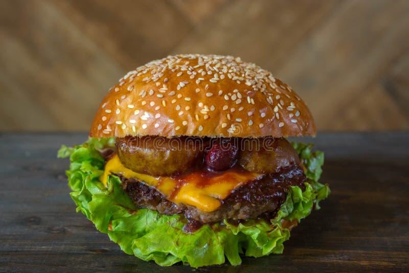 Burger, σάντουιτς χάμπουργκερ με cutlet του κιμά, λείωσε το τυρί, το κεράσι μούρων και το αχλάδι Πλάγια όψη σχετικά με ένα ξύλινο στοκ φωτογραφία με δικαίωμα ελεύθερης χρήσης