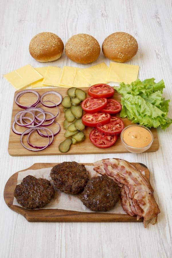 Burger συστατικά σε έναν άσπρο ξύλινο πίνακα, πλάγια όψη closeup στοκ φωτογραφίες
