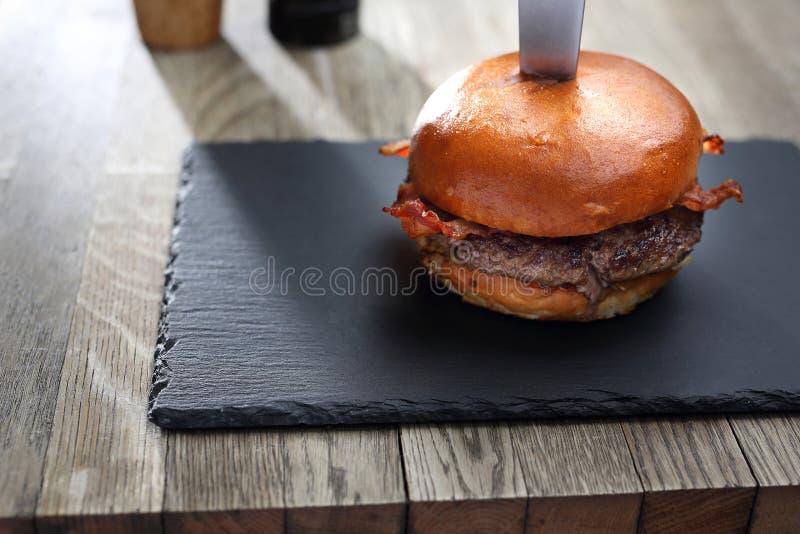 Burger Ψημένο στη σχάρα cutlet βόειου κρέατος σε ένα κουλούρι στοκ εικόνες