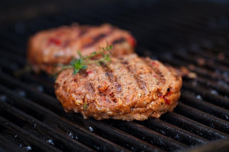 Burger auf Parteisommergrill grillen mit Flamme lizenzfreie stockbilder