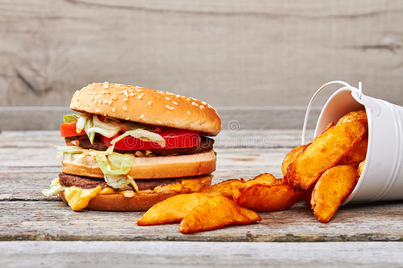 Burger with beef and cheese. Fries on wooden surface. Popular business idea royalty free stock image