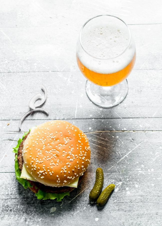 Burger with beer in a glass. On white wooden background royalty free stock photo