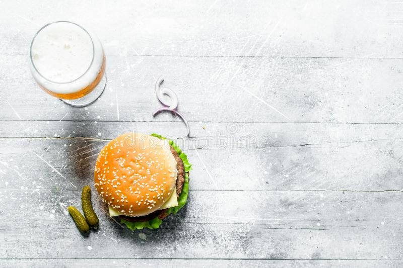 Burger with beer in a glass. On white wooden background royalty free stock image