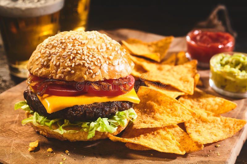 Burger with beer and nachos appetizers stock images