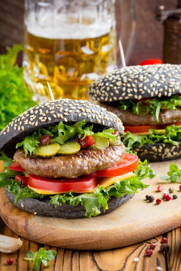 Burger with black bun, beef cutlet, tomato, cheese, salad, delicious homemade sandwich with beer, food royalty free stock photo