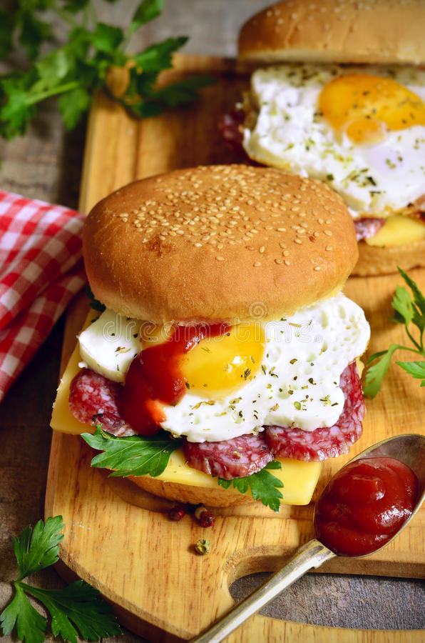 Burger with cheese,salami and fried egg. Burger with cheese,salami and fried egg on a cutting board royalty free stock images