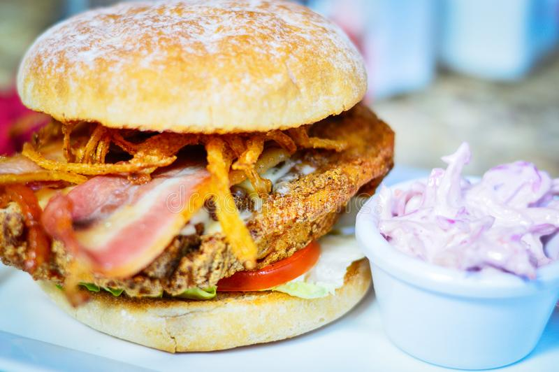 Burger with Chicken, Bacon and Fried Onions. Closeup of Burger with Chicken, Bacon, Fried Onions & Coleslaw stock photo