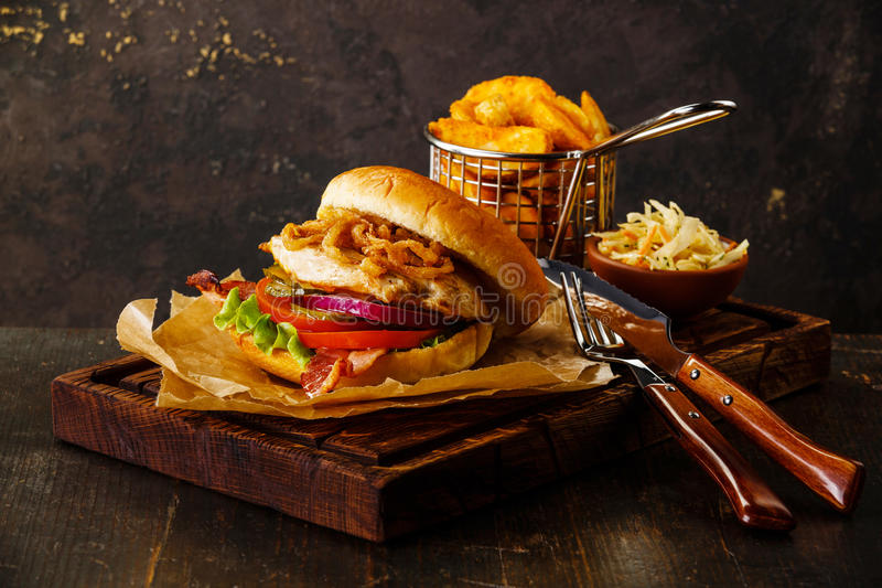 Burger with chicken breast and fried onions. With coleslaw and potato wedges on dark background royalty free stock photography