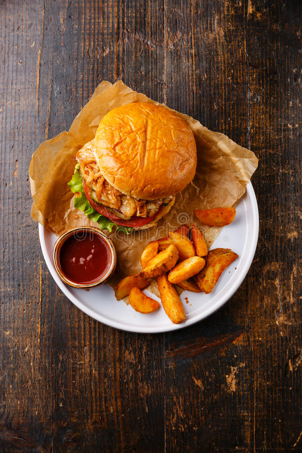 Burger with chicken breast and fried onions with potato wedges. On plate on dark wooden background stock photos