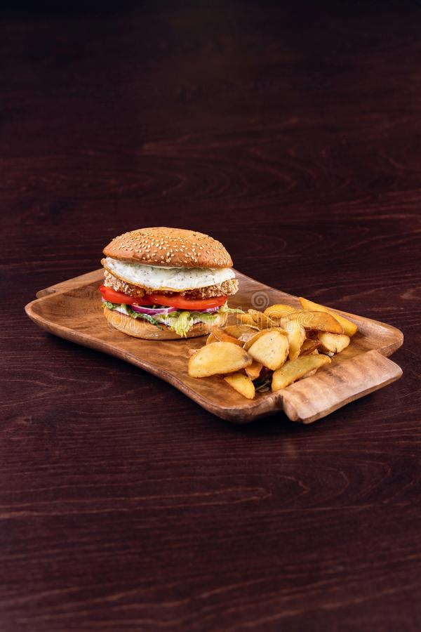 Burger with chicken breast with potato wedges on wooden background. Burger with chicken breast with potato wedges royalty free stock photo