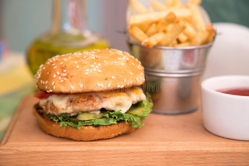 Burger with chicken cutlet and fries.  royalty free stock photo