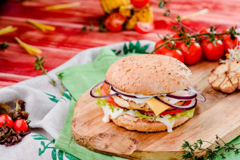 Burger with chicken cutlet, tomatoes, cheese, onoins, lettuce and red sauce on a wooden board on a red wooden background. Decorated with napkins, chili pepper stock images