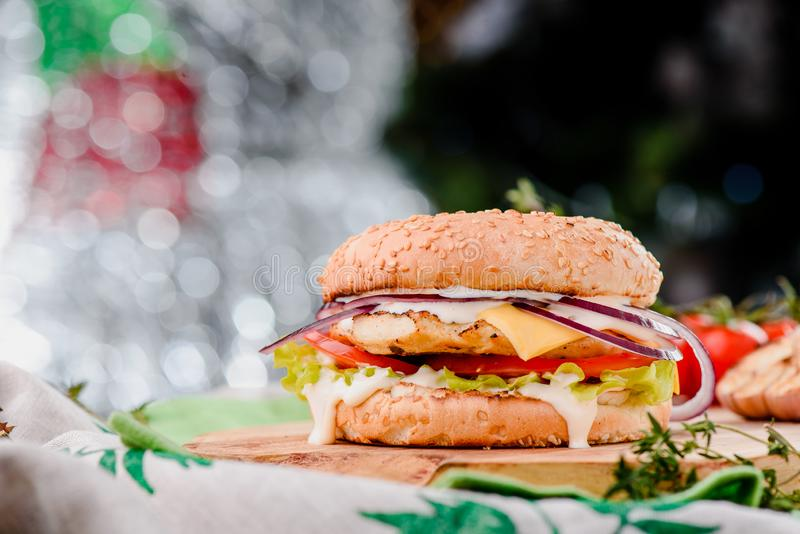 Burger with chicken cutlet, tomatoes, cheese, onoins, lettuce and red sauce on a wooden board on a red wooden background. Decorated with napkins, chili pepper royalty free stock photos
