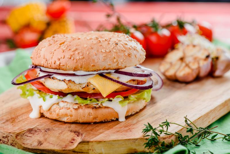 Burger with chicken cutlet, tomatoes, cheese, onoins, lettuce and red sauce on a wooden board on a red wooden background. Decorated with napkins, chili pepper stock photos