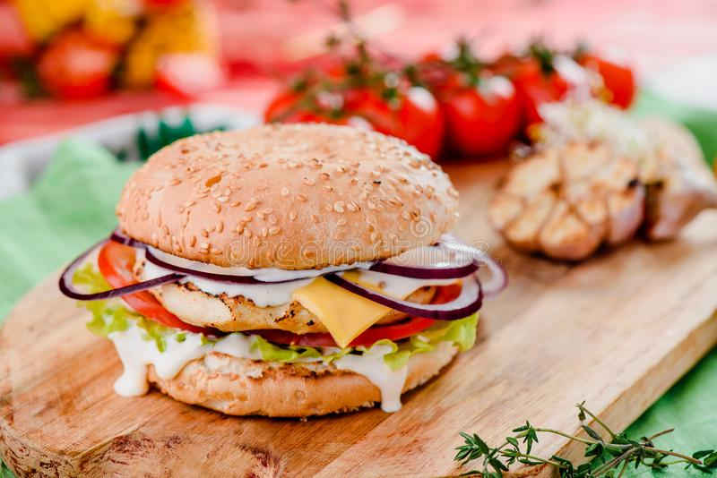 Burger with chicken cutlet, tomatoes, cheese, onoins, lettuce and red sauce on a wooden board on a red wooden background. Decorated with napkins, chili pepper stock image