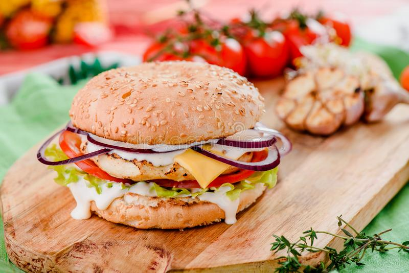 Burger with chicken cutlet, tomatoes, cheese, onoins, lettuce and red sauce on a wooden board on a red wooden background. Decorated with napkins, chili pepper royalty free stock images