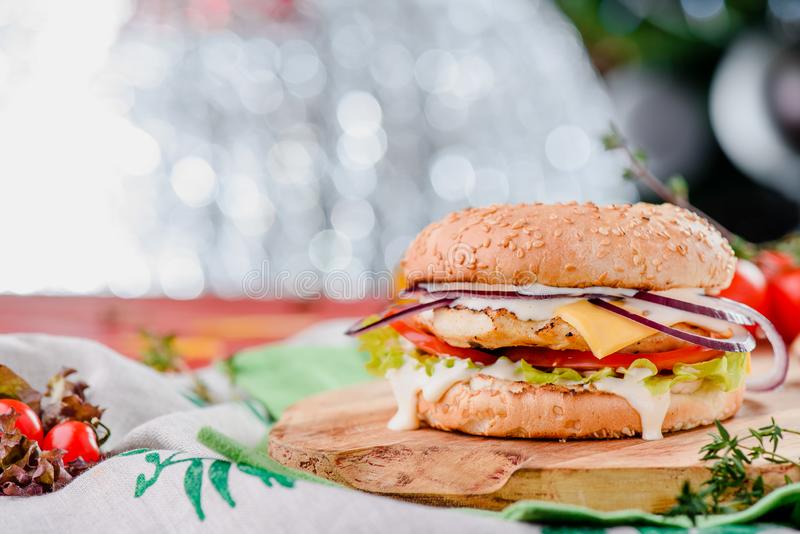 Burger with chicken cutlet, tomatoes, cheese, onoins, lettuce and red sauce on a wooden board on a red wooden background. Decorated with napkins, chili pepper royalty free stock photo