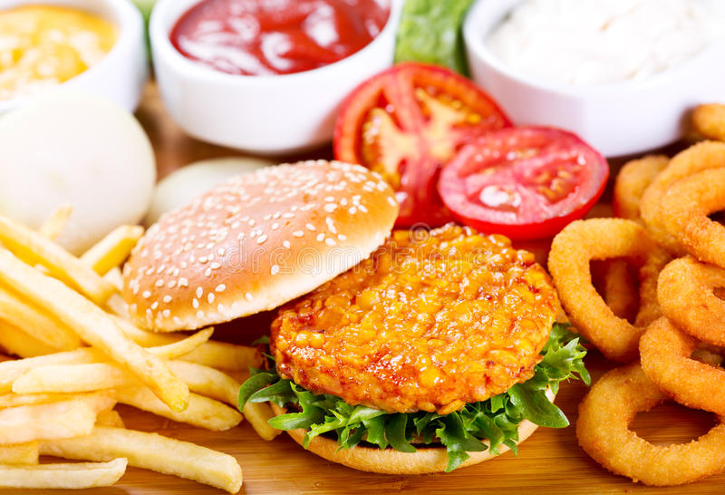 Burger with chicken and fries. On wooden table stock photos