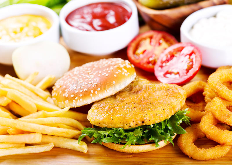 Burger with chicken and fries. On wooden table stock images