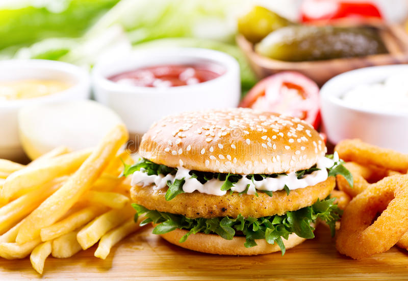 Burger with chicken and fries. On wooden table stock photography