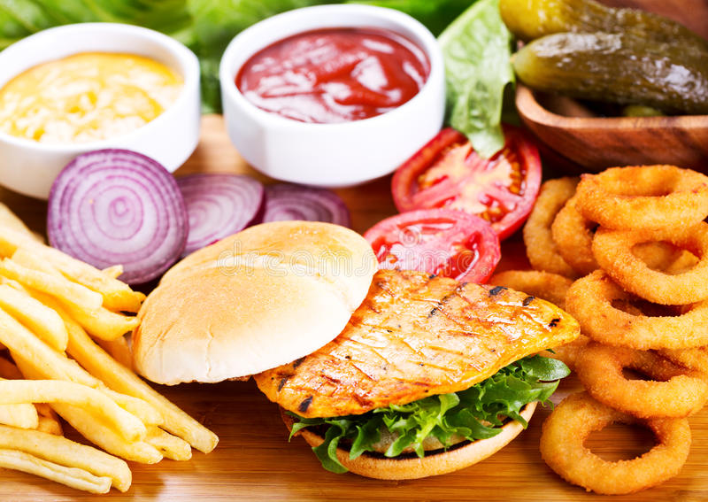 Burger with chicken and fries. On wooden table stock photo