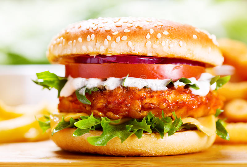 Burger with chicken and fries. On wooden table royalty free stock photos