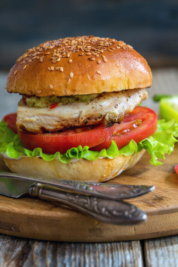 Burger with chicken, hot sauce and salad. Burger with chicken and salad on a wooden board royalty free stock photo