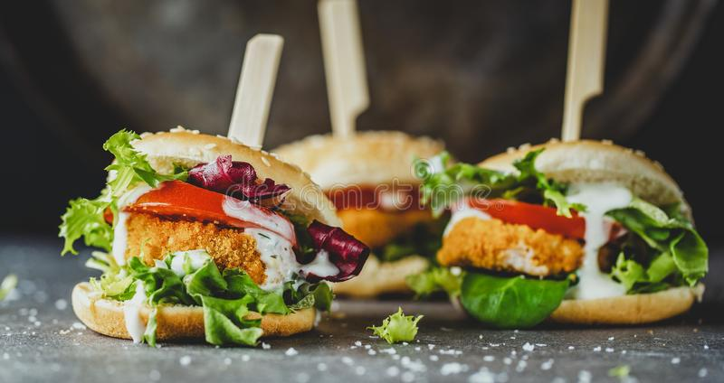 Burger with chicken patty and vegetables. Tasty appetizing burger with chicken patty nuggets and vegetables on dark background. Closeup. Horizontal stock photo