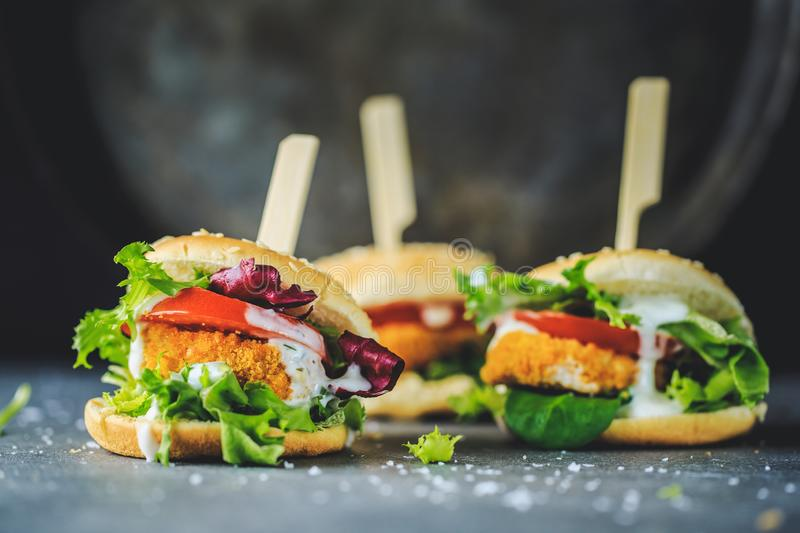Burger with chicken patty and vegetables. Tasty appetizing burger with chicken patty nuggets and vegetables on dark background. Closeup. Horizontal royalty free stock photography