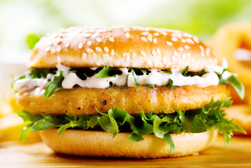 Burger with chicken. On wooden table royalty free stock photography