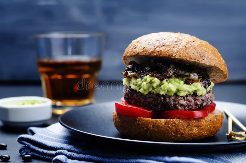 Burger der schwarzen Bohne mit gestampfter Avocado, karamellisierten Zwiebeln und zu lizenzfreie stockfotografie