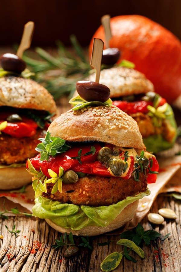 Burger di verdura, hamburger di manichino con aggiunta di peperoni grigliati, lattuga, erbe fresche e capperi fotografia stock