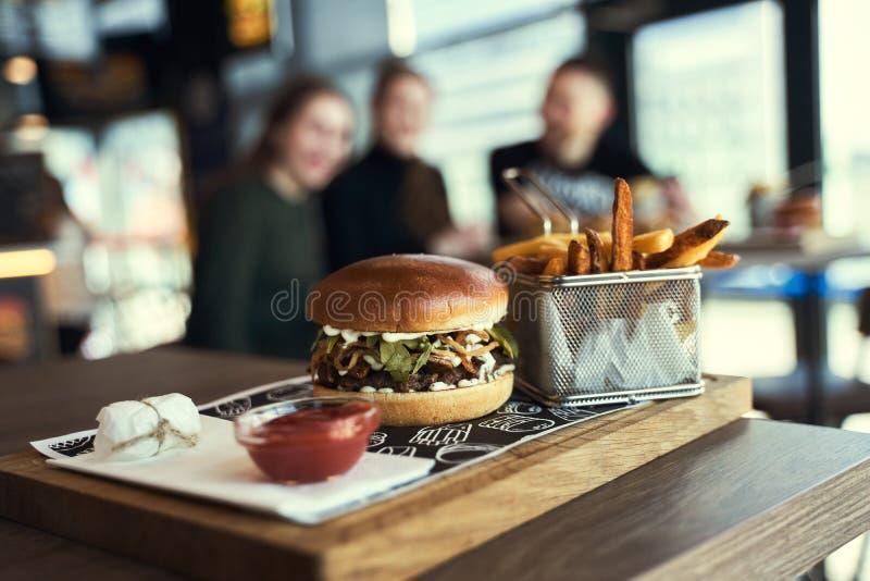 Burger e patatine fritte di manzo artigianale su tavolo di legno su fondo nero fotografia stock libera da diritti