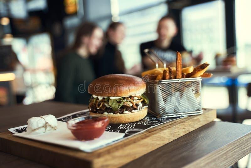 Burger e patatine fritte di manzo artigianale su tavolo di legno su fondo nero fotografie stock libere da diritti
