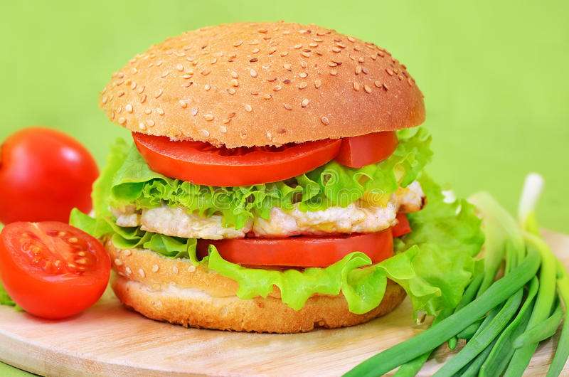 Burger fast food. On a kitchen board with tomatoes and green onions stock image