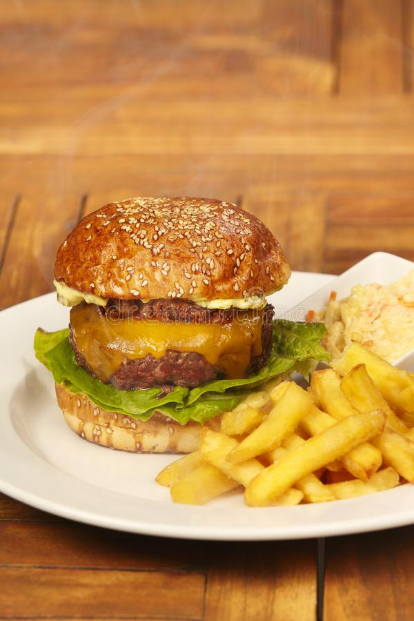 Burger with french fries and coleslaw salad on plate. Luxury beef burger in bun with cheese, bacon marmelade, lettuce, french fries and coleslaw salad royalty free stock photo