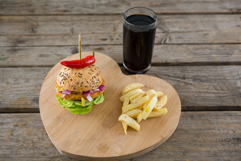 Burger with French fries on heart shape cutting board by drink stock photo