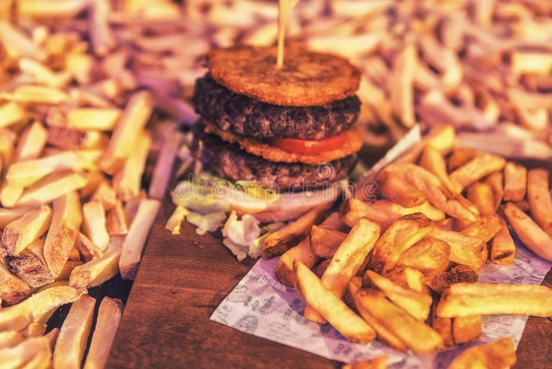 Burger and fries. With heaps of raw French fries in the background stock photos